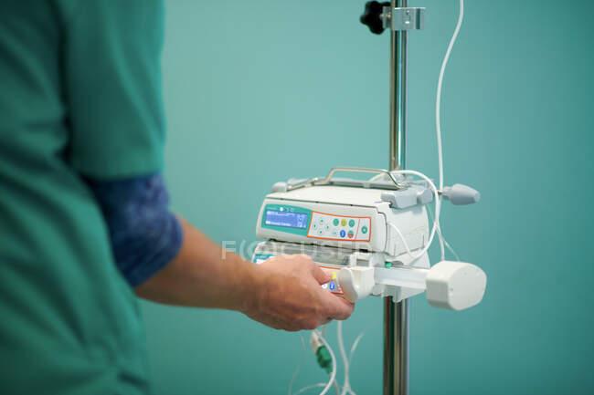 Vista lateral del médico anónimo de cultivo en uniforme médico que controla IV en la bomba de infusión moderna en el quirófano - foto de stock