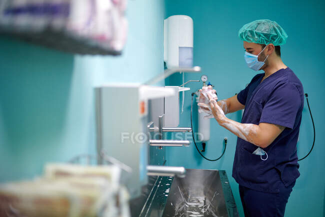 Side view of anonymous young male doctor in medical uniform and mask washing hands with soap before surgery in operating room — Stock Photo