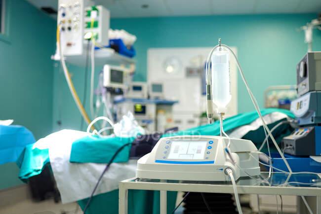 Infusionspumpe mit IV-Beutel vor der Operation auf einem Tisch in der Nähe der Couch im Operationssaal voller moderner Geräte im Krankenhaus platziert — Stockfoto