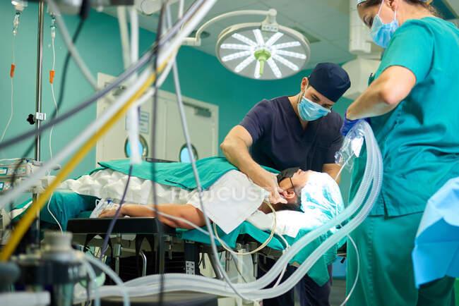 Низкий угол анонимного концентрированного медбрата в униформе и маске, покрывающий неузнаваемого пациента стерильным одеялом перед операцией в современной больнице — стоковое фото
