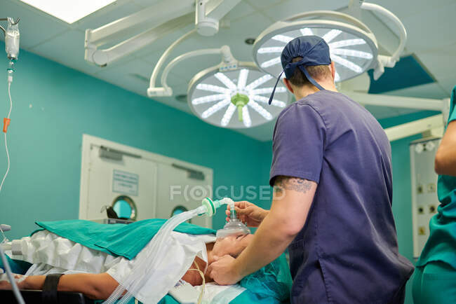 Side view of anonymous male anesthesiologist in medical uniform and cap holding anesthesia mask on face of unrecognizable patient lying on couch in operating room — Stock Photo