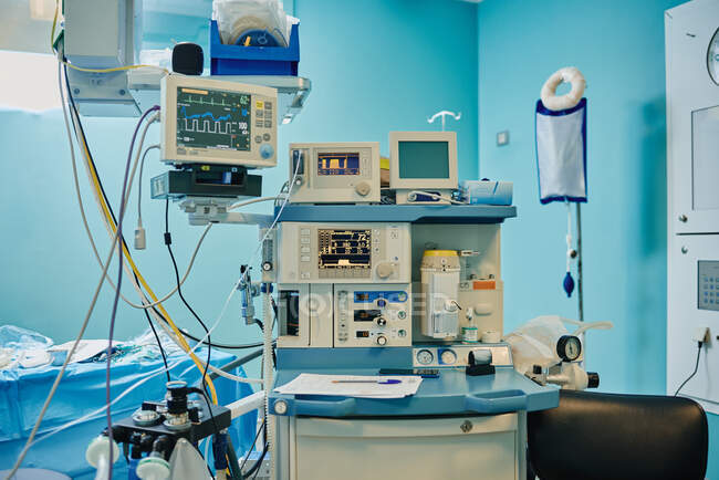 Cardiac event monitor and various modern medical devices in operating room during surgery — Stock Photo