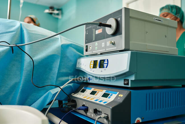 From below of anonymous female doctors standing near coagulator and endoscopic equipment placed near operating table during medical procedure — Stock Photo