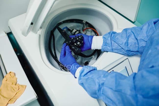 Von oben von der Ernte unkenntlich Arzt in sterilen Handschuhen und Mantel setzen Endoskop in Zentrifuge der Desinfektionsmaschine nach dem Eingriff — Stockfoto