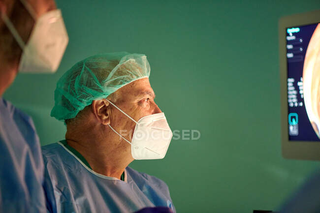 Side view of anonymous doctors in surgical gowns and masks looking at monitor while examining patient with endoscope before operation in modern clinic — Stock Photo