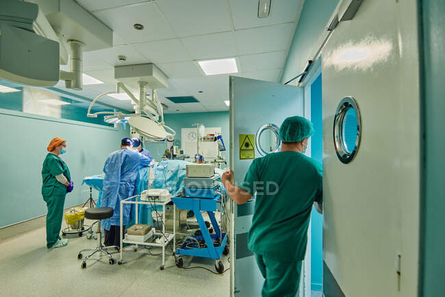 Back view of unrecognizable medical assistant leaving operating room while group of doctors performing surgery in modern clinic — Photo de stock