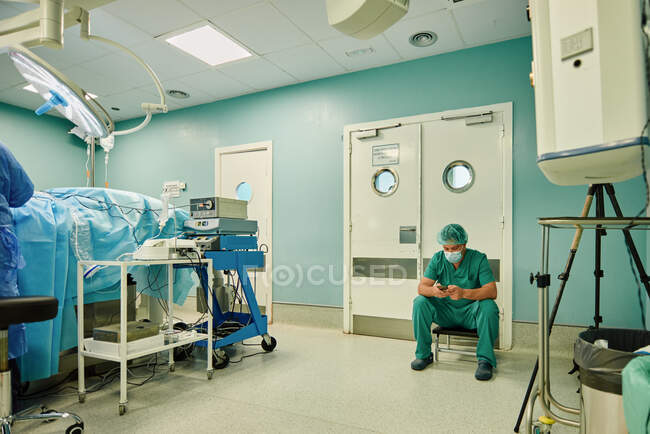 Anonymous young male doctor in green medical uniform and mask messaging on mobile phone while sitting in operating room after surgery — Photo de stock