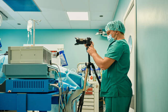 Side view of unrecognizable young male medical photographer in sterile mask and uniform taking pictures on professional camera during surgery in modern operating room - foto de stock
