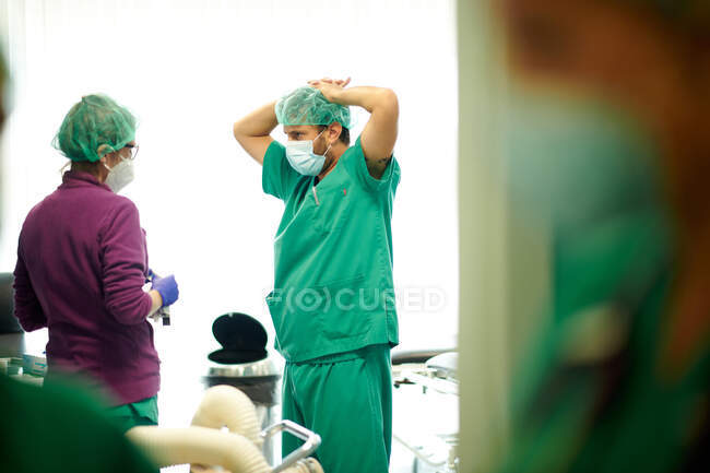 Side view of anonymous male and female doctors in medical uniforms and masks discussing results of treatment in hospital - foto de stock