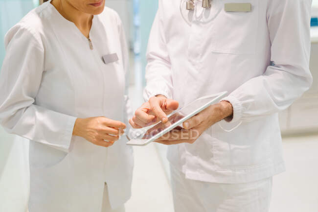 Crop anonymous dentists in medical robes examining teeth condition on x ray scan on tablet while working together in modern dental clinic — Fotografia de Stock