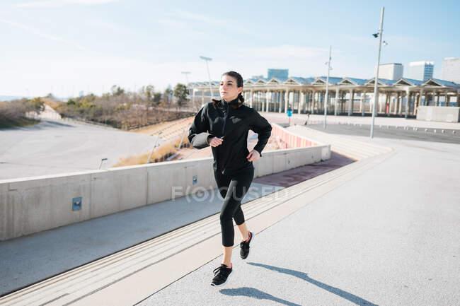 Полное тело спортивная молодая бегунья в черной спортивной одежде бегает по асфальтовой дороге в солнечном пригороде и смотрит в сторону — стоковое фото