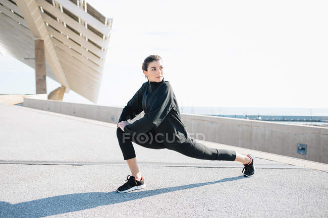 Full length determined young sportswoman in activewear stretching legs while warming up on road in suburb — стоковое фото