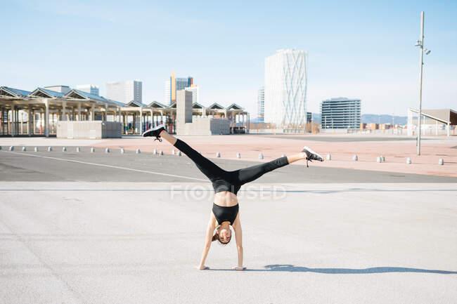 Вид сзади Полная длина определяется спортсменка в плотно активной одежде делать упражнения на руках на асфальтированной дороге на солнечном пригороде с открытыми ногами — стоковое фото