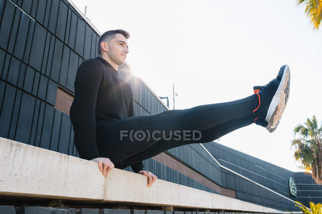 Full length fit strong sportsman in black activewear performing L sit exercise on concrete fence railing during intense work out on sunny street — Stock Photo
