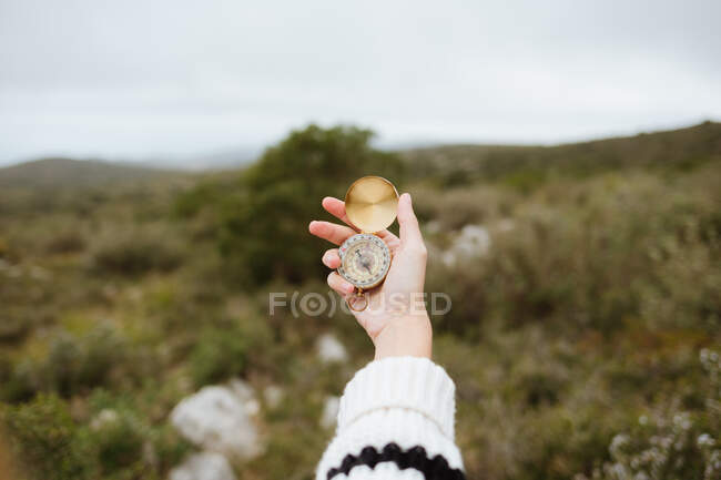 Crop anonymous female tourist using compass on mountain with rough stones in daylight - foto de stock
