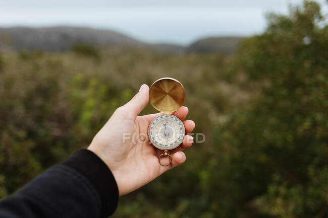 Crop anonymous person tourist using compass on mountain with rough stones in daylight — Stock Photo