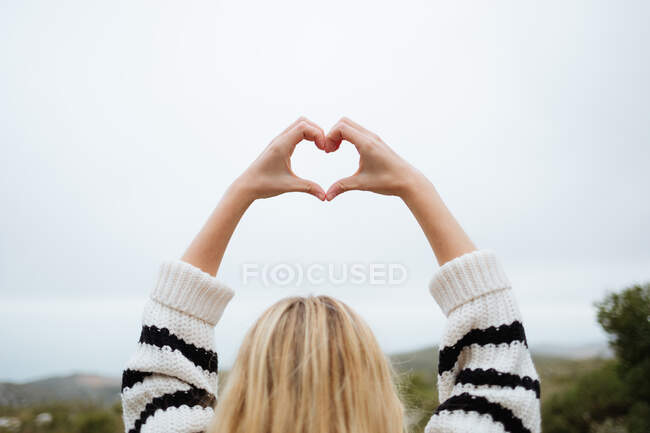 Back view of crop anonymous female tourist with raised arms demonstrating love symbol against mount under white sky — Foto stock
