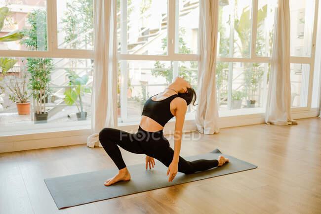 Анонимная женщина в спортивной одежде откидывается на коврик, практикуя йогу у окна дома — стоковое фото
