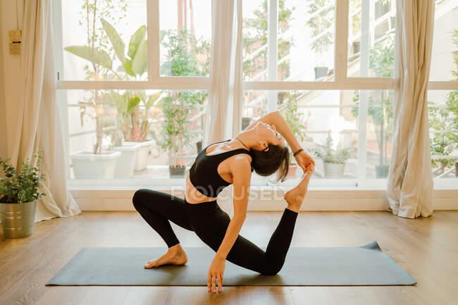 Вид сбоку молодой босиком женщины в спортивной одежде, сидящей в эка пада раджакапотасана позы во время практики йоги на мат в доме — стоковое фото