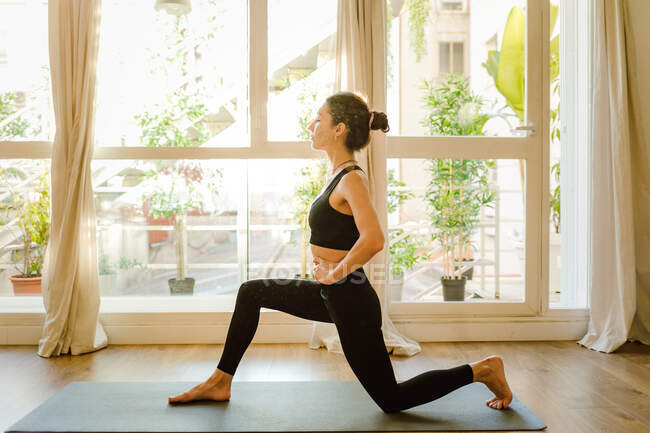Side view of young barefoot female in sportswear standing in Anjaneyasana pose on yoga mat against window in house — стоковое фото