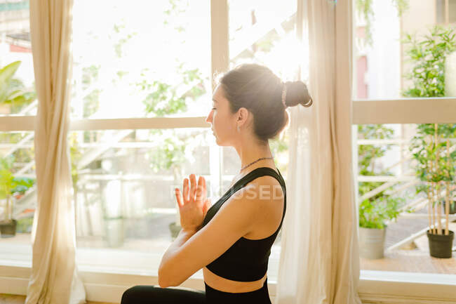 Young flexible dreamy female in sportswear performing Padmasana pose with closed eyes on yoga mat in house — Photo de stock