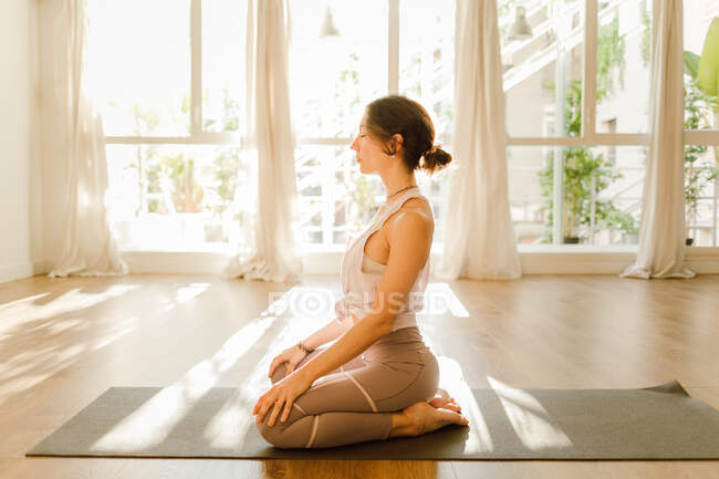 Side view of young dreamy female in sportswear practicing yoga with arms behind back while sitting with closed eyes in sunlight — Photo de stock