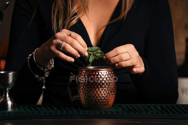 Cropped unrecognizable self assured focused young female barkeeper with long blond hair in stylish outfit decorated cocktail with lemon slices while standing at counted in stylish bar — Stock Photo