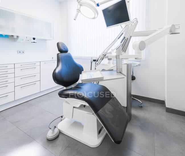 Внутрішня частина акуратної легкої стоматологічної клініки з синім кріслом і сучасним буровим апаратом. — стокове фото