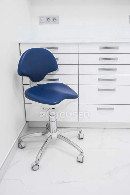 Стильный дизайн интерьера современной светлой клиники с белой мебелью и синим креслом — стоковое фото