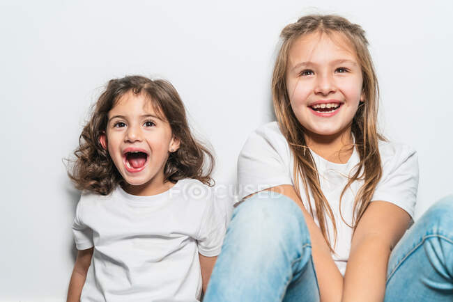 Hermanitas lindas felices en camisa blanca y jeans sentados en el suelo contra la pared en casa con sonrisas de dientes - foto de stock