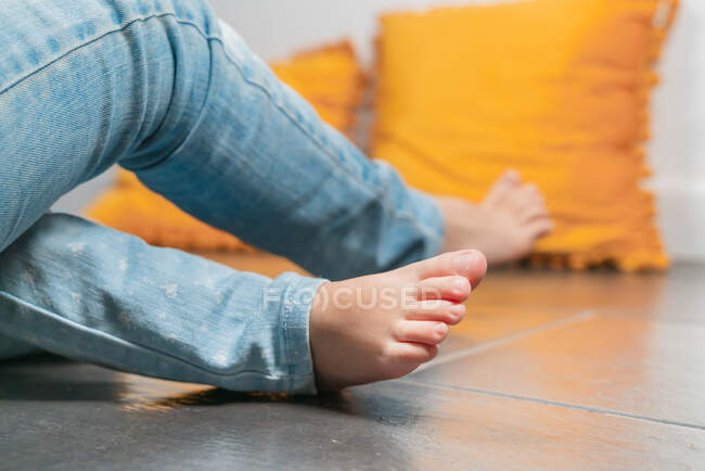 Crop anonymous barefoot sisters legs wearing blue jeans sitting on floor together at home — Stock Photo