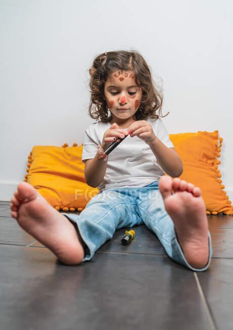 Menina pouco emocional no desgaste casual com desenhos de batom vermelho no rosto feliz enquanto sentado no chão em casa — Fotografia de Stock