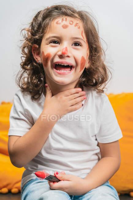 Радостная маленькая девочка в повседневной одежде с рисунками красной помады на счастливом лице, касающемся шеи и отворачивающемся, сидя на полу — стоковое фото