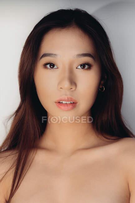 Ritratto di giovane donna cinese nuda che guarda la macchina fotografica su sfondo bianco — Foto stock