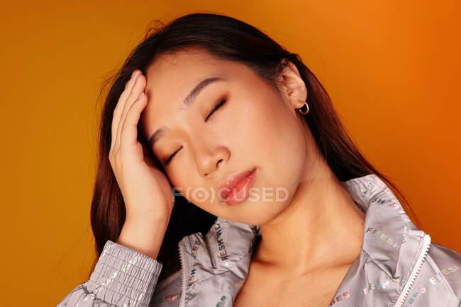 Jovem chinesa preocupada com olhos fechados sobre fundo amarelo — Fotografia de Stock