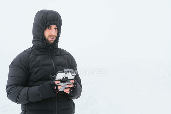 Focused bearded male wearing warm black jacket with hood standing on snowy terrain with drone remote control and looking away — Stock Photo