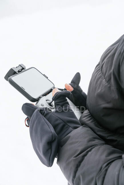Cropped unrecognizable male wearing warm black jacket with hood standing on snowy terrain with drone remote control — Stock Photo