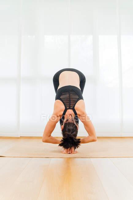 Все тело безликой женщины медитирует в Big Toe asana во время практики йоги на спортивном коврике в студии — стоковое фото