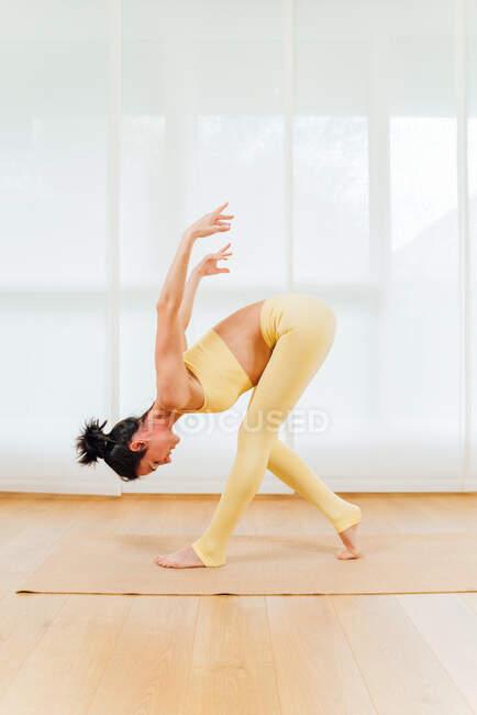 Полный вид сбоку тела сфокусированной женщины, наклоняющейся вперед с ногой на цыпочках в Standing Forward Bend with Shoulder Opener asana — стоковое фото