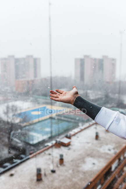 Crop anonymous person catching falling snowflakes while standing on balcony in modern city on cold winter day — Stock Photo