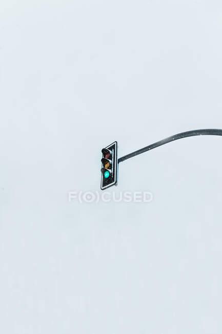 Dal basso semafori contemporanei che mostrano il segnale verde situato contro grigio cielo cupo — Foto stock
