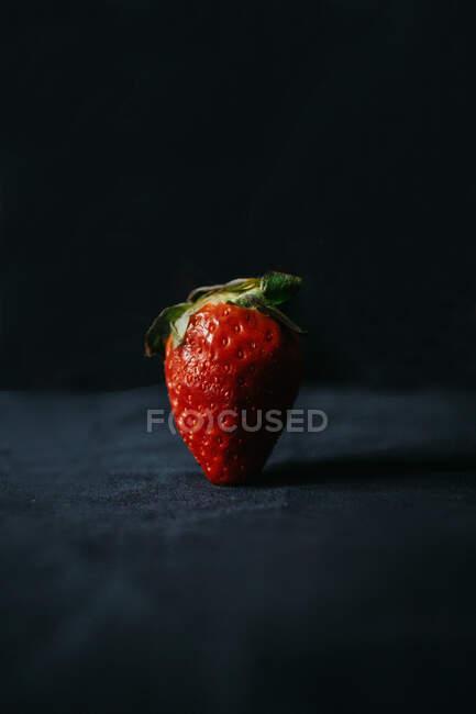 Colorida fresa dulce sabrosa con pedicelo verde en la parte superior y pequeñas semillas en superficie desigual - foto de stock