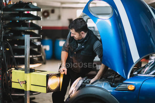Young focused bearded maintenance man repairing contemporary auto against bright light and looking away in workshop — Stock Photo