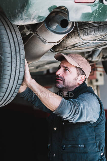 Young attentive bearded auto master in cap revising transport wheel in workshop in sunlight — Stock Photo