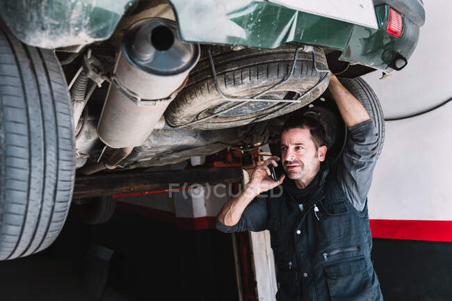 Young focused male auto master speaking on cellphone while checking up rear part of transport and looking away in workshop — Stock Photo
