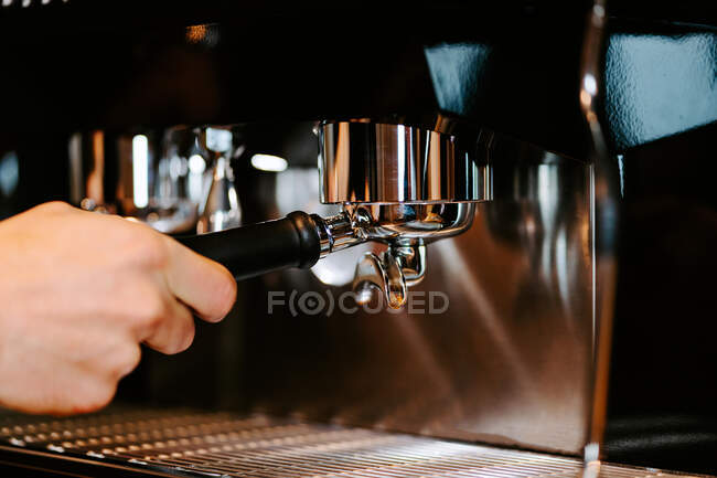 Unrecognizable crop bartender with portafilter preparing beverage in modern coffeemaker while working in cafe — Stock Photo