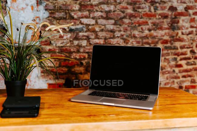 Сучасна нетбук розміщена на дерев'яному прилавку в кав'ярні з інтер'єром у стилі лофта. — стокове фото