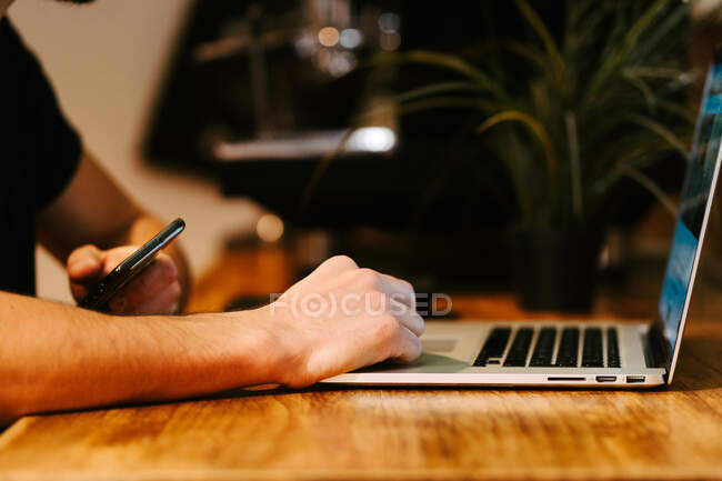 Side view delighted male barista browsing laptop while sitting at counter in coffee shop and working — Stock Photo