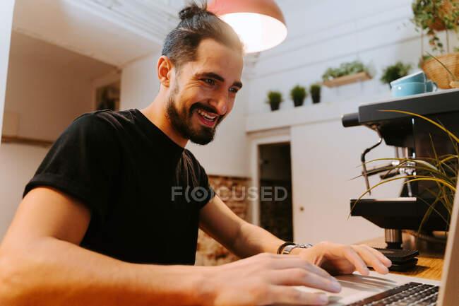 Низкий угол восторженный мужчина бариста просматривает ноутбук, сидя за стойкой в кафе и работы — стоковое фото
