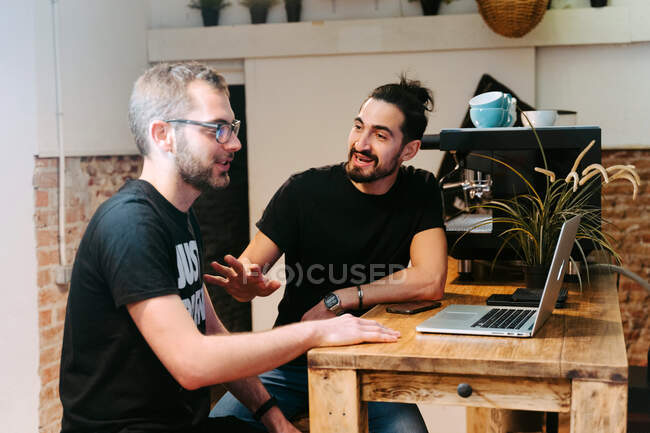 Male baristas sitting at counter with laptop in cafe and talking about work issues — Stock Photo